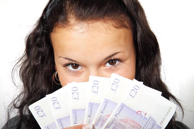 お金を持つ若い女性