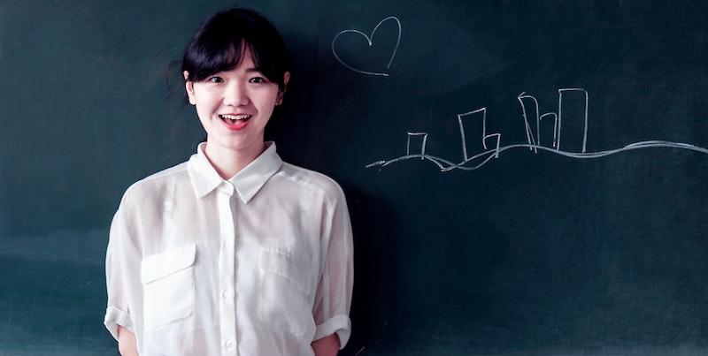 黒板の前に立つ女子大学生