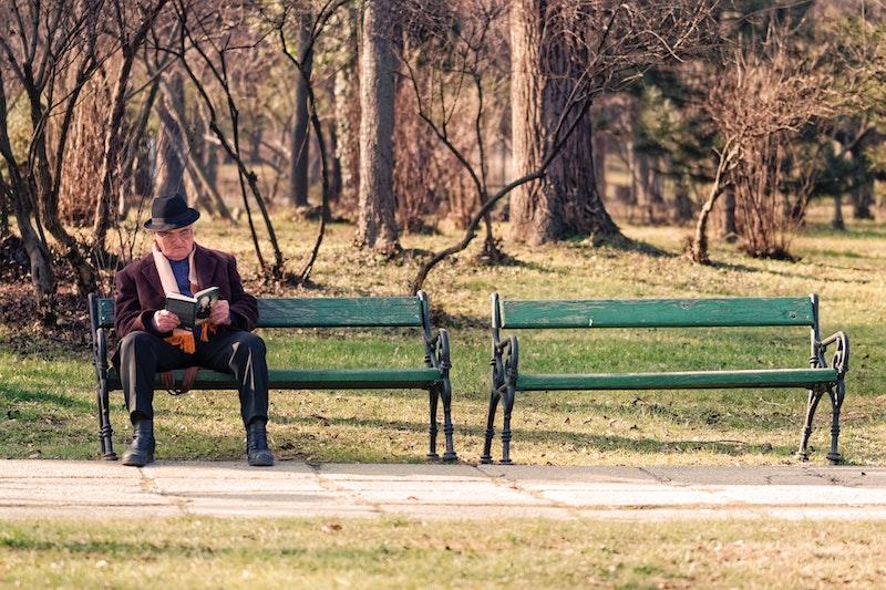ベンチで本を読む男性教授