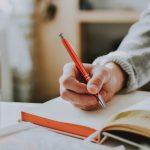 赤いペンを持つ